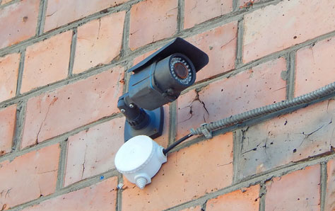 Close up picture of a CCTV camera on brick building