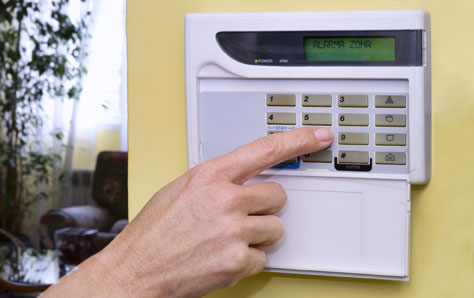 An image of a homeowner setting alarm for home security
