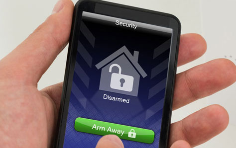 Close-up Of Businessperson Hands Arming Entrance Security System With Mobile Phone