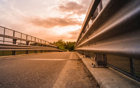 An image of road and crash barriers at the sunset