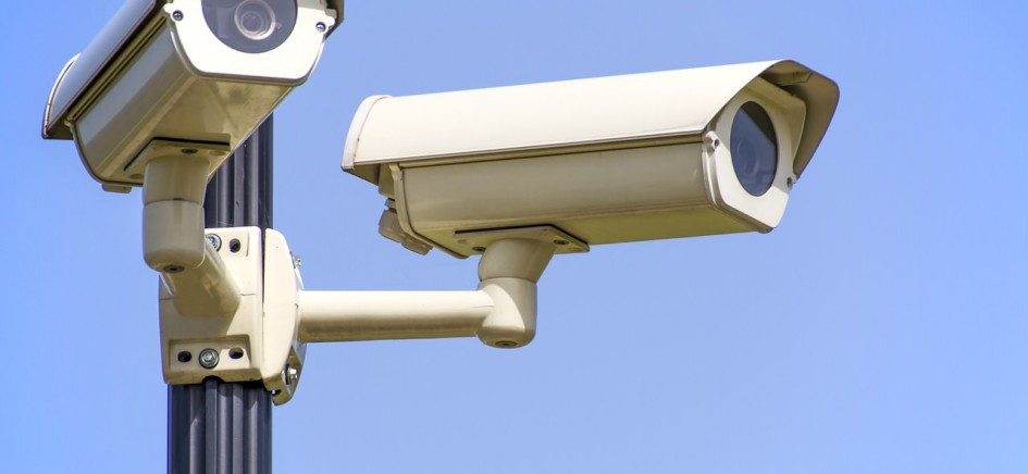 an image of two cctv cameras mounted on a pole with the sky as a background