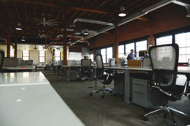 A picture of an empty office with only 2 employees working
