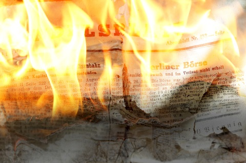 A picture of a newspaper on fire