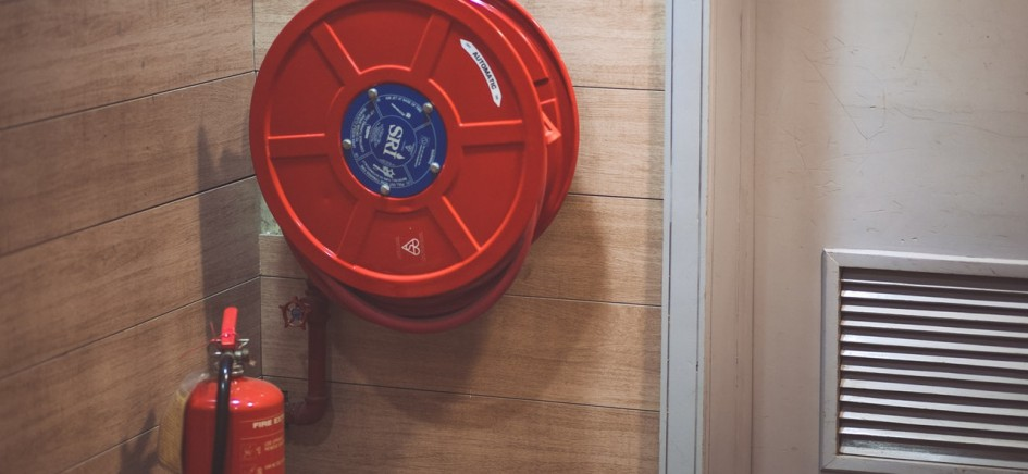 A fire extinguisher and hose reel on a wall - legal requirements of the fire safety order