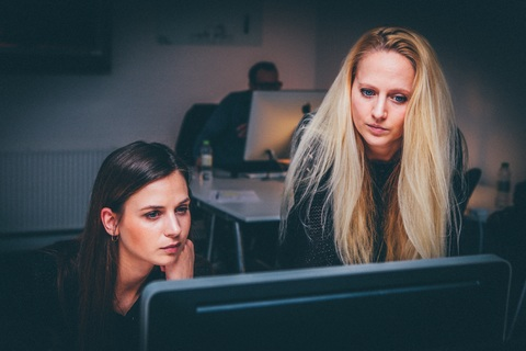 A picture of 2 female employees working in a dark office