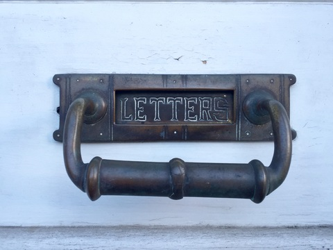 A picture of a letter box on a door